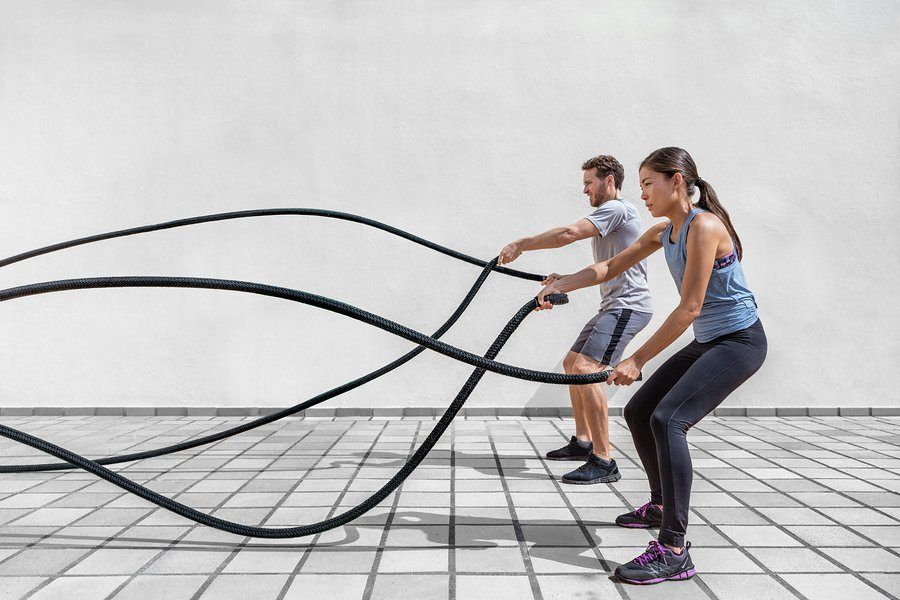Fitness people exercising with battle ropes at gym
