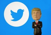 Donald Trump Bobble Head figure standing in front of a Twitter logo