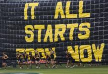 AFL team Tigers run through banner