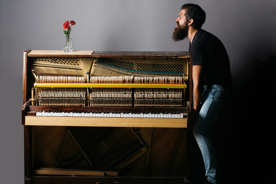 handsome bearded strong man with stylish hair mustache and beard trying to move old wooden or wood open piano with keyboard and glass vase with red rose flowers on grey background copy space