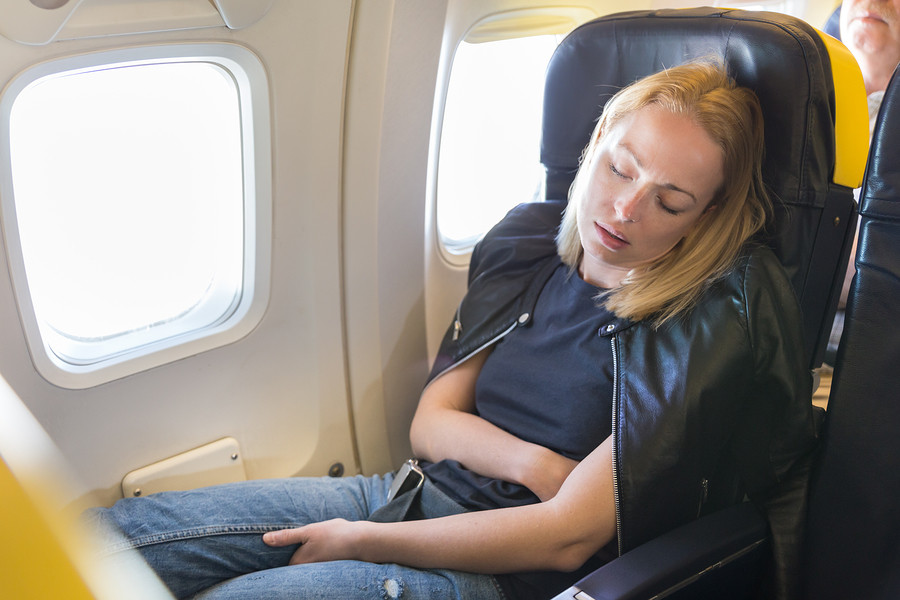 Tired blonde casual caucasian lady napping on exit window seat while traveling by airplane. Commercial transportation by planes.