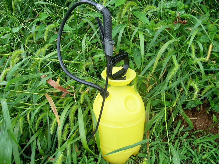 Photo of a chemical sprayer sitting in tall grass.