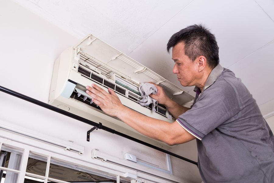 Series of technician servicing the indoor air-conditioning unit. Cleaning with cloth.
