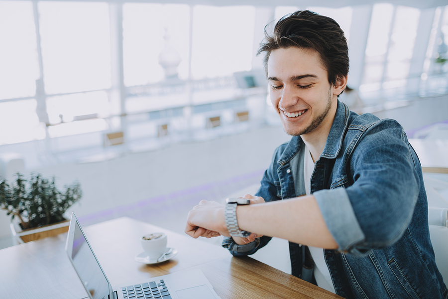 Young stylish man working on a macbook or laptop in cafe while having coffee and checking his nice watch. Happy guy in jeans jacket pointing at clock face