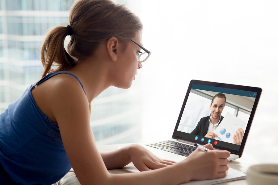 Woman in glasses watching business webinar and taking notes. Aspiring female entrepreneur watching free video lesson with businessman showing potential profits for startup business on laptop screen.