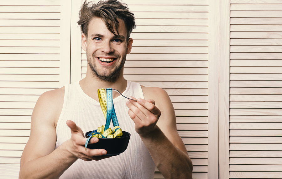 Fitness lifestyle and regime idea. Man with unshaven face holds bowl and fork with measuring tape. Weight management and sportive diet concept. Guy with happy face on background of beige jalousie.