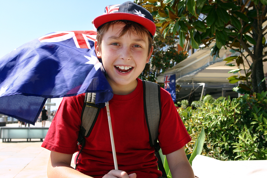 Happy patriotic young boy flying a flag on summer national day.