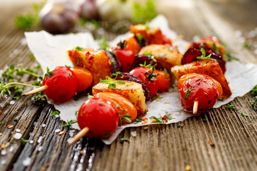Vegetarian skewers with halloumi cheese, cherry tomatoes, red onion and fresh herbs on a wooden rustic table