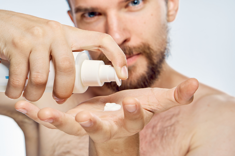 man applies cosmetic cream on hand, portrait.