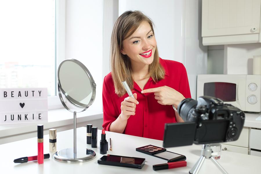 Professional beauty blogger showing mascara, eyeliner, eyelash cosmetics to video camera