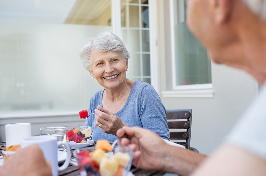 Happy senior woman eating fresh fruits during breakfast. Cheerful old lady with enjoying healthy breakfast with her husband outdoor. Elderly couple in conversation enjoying fruit on the balcony.