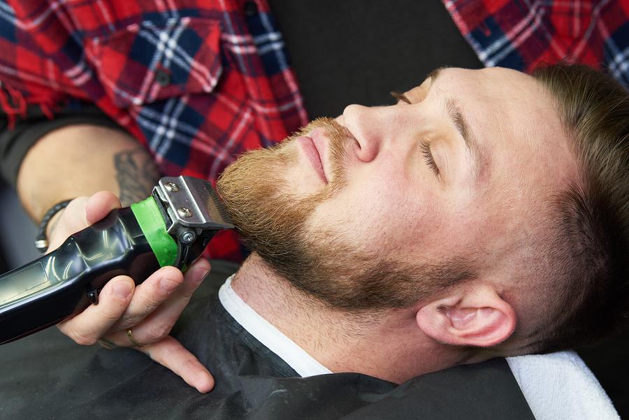 Beard care. man while trimming his facial hair cut at the barbershop