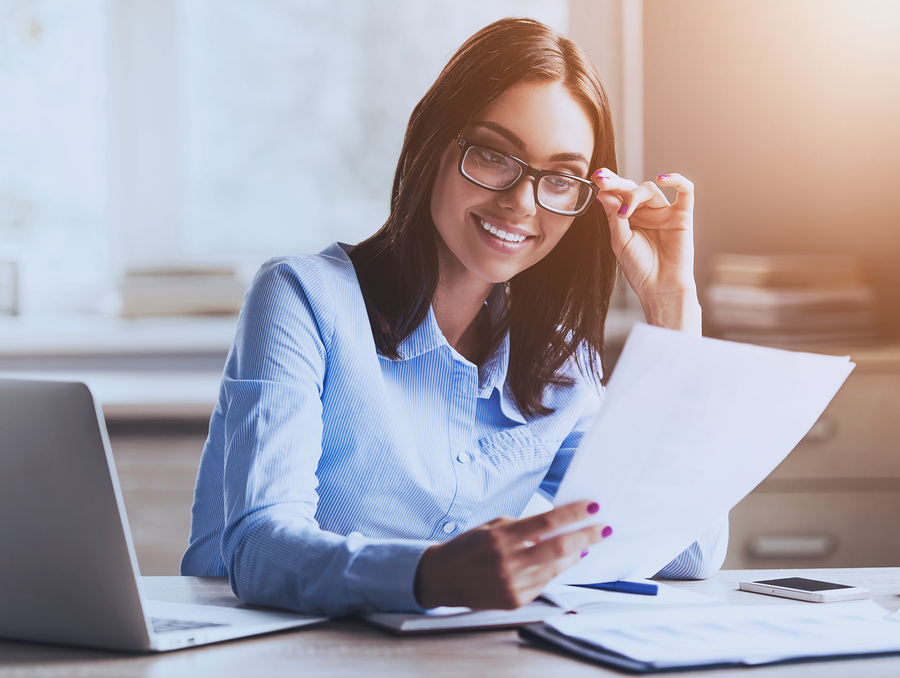 Young Pretty Lady Reading Documents and Smiling while Working in Office. Accountant Manager. Office Administrator. Workday in Office. Work and Job Concepts. Smiling Businesswoman. Business Concept.