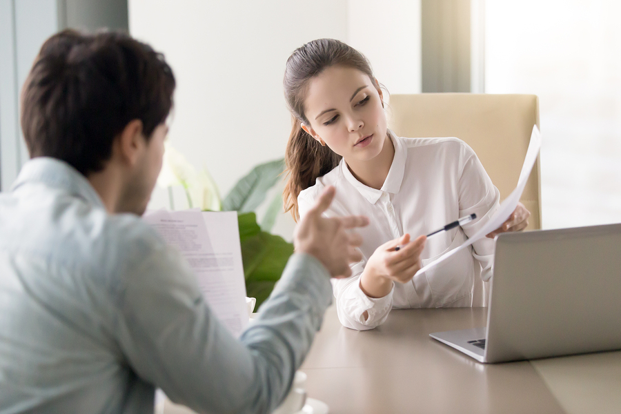 Businessman and businesswoman discussing papers concerning new business project during meeting at office, colleagues preparing important documents, partners negotiating under contract, teamwork