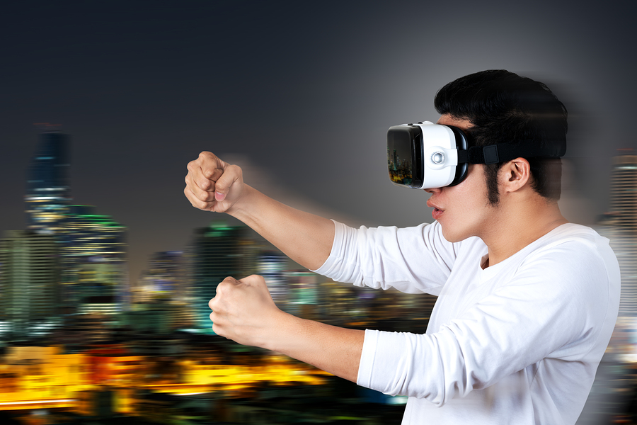 Young asian man in casual white outfit holding or wearing VR glasses goggles playing car racing video game, shocked and amazed on motion city background. Virtual reality of gamer experience concept.