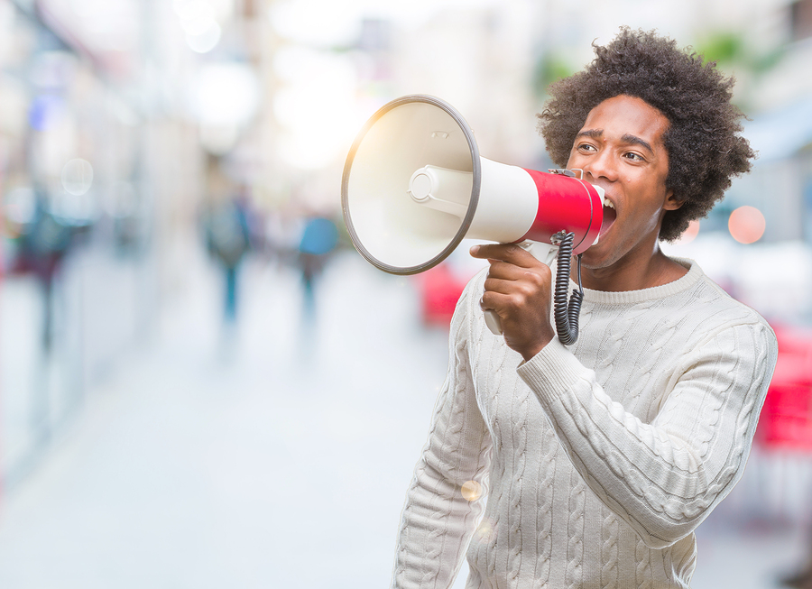Young handsome afro american black man shouting through megaphone