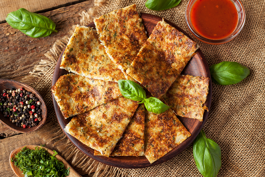 Breadsticks made of cauliflower, cheese and herbs, served with fresh basil leaves and red sauce