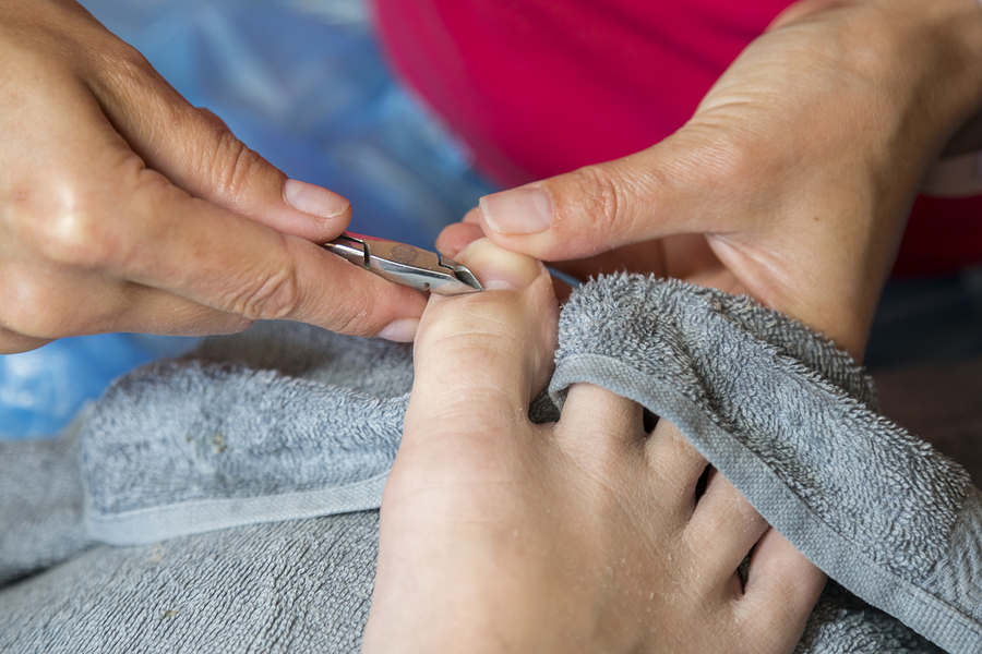 Master using professional instruments when doing pedicure. Pedicure treatment in beauty salon. Close up concept