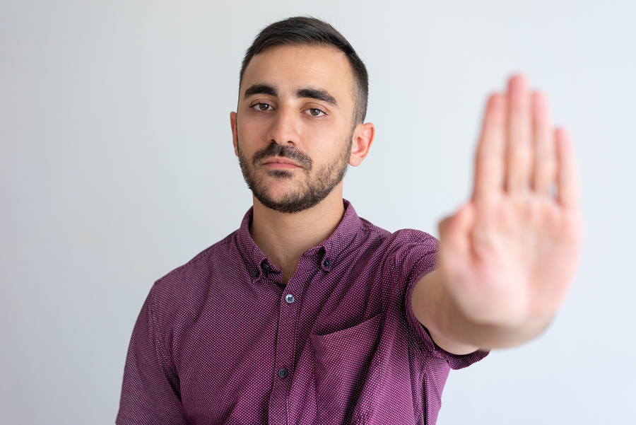 Strict businessman in casual gesturing stop. Young man raising hand and showing palm in prohibited sign. Prohibition concept