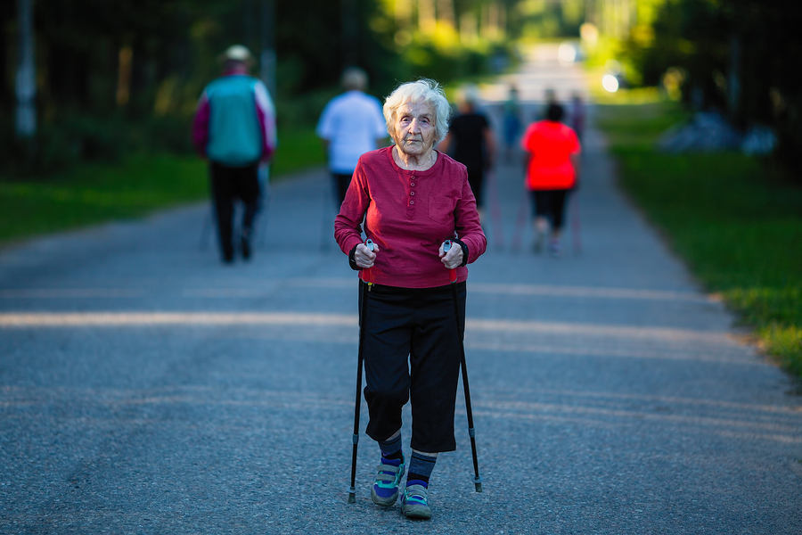 Elderly woman engaged in Nordic walking with sticks.