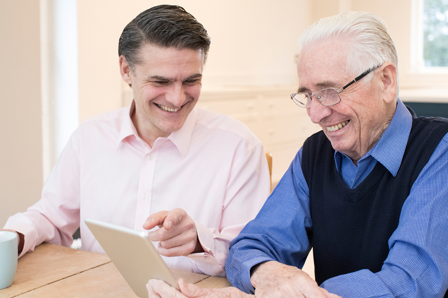 Male Neighbor Showing Senior Man How To Use Digital Tablet
