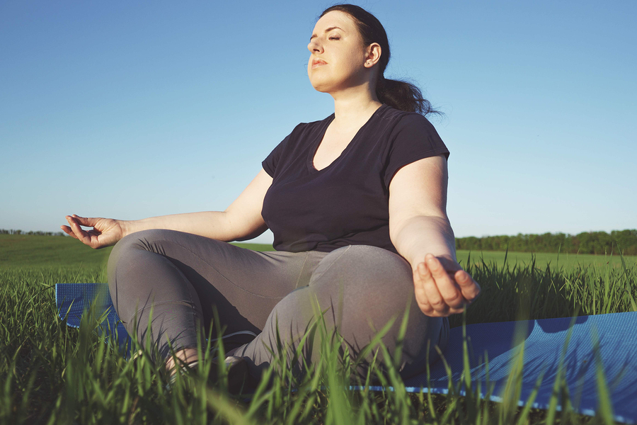 Body positive, yoga, meditation, tranquility, relax. Overweight woman meditating sitting at yoga mat outdoors. high self esteem, no complex, free your mind concept