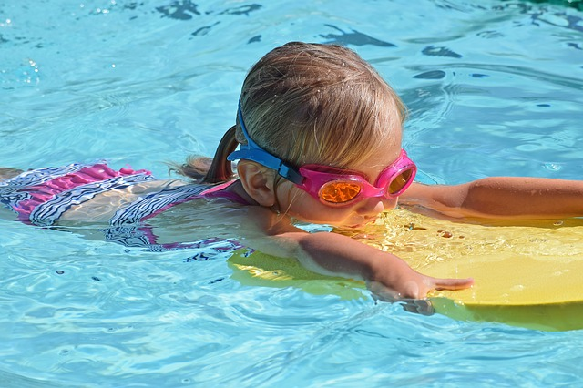 Young girl swimming in pool with goggles