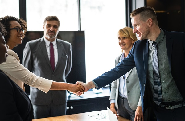 Two people shaking hands in welcoming business meeting