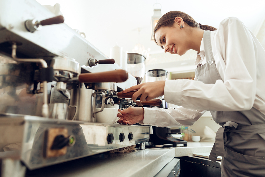 Beautiful young girl barista preparing coffee. Young barista girl makes flavored coffee for the client. Coffee machine for making delicious natural coffee. The concept of the restaurant business.