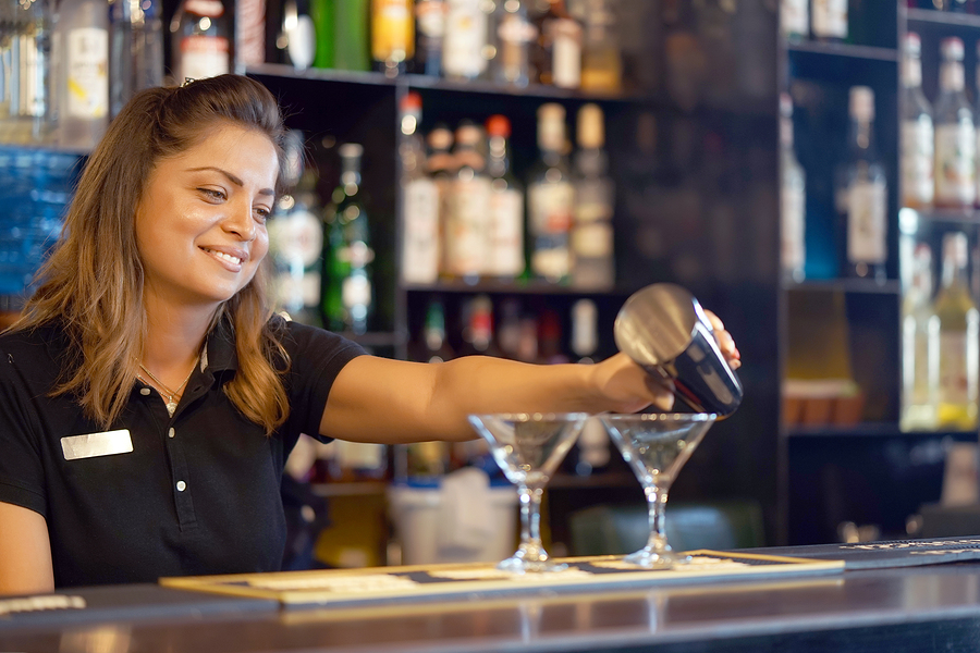 Professional bartender woman pours a fresh cocktail to the customers of the hotel bar. The bartender girl pours a cocktail. The concept of service. Focus on the bartender.