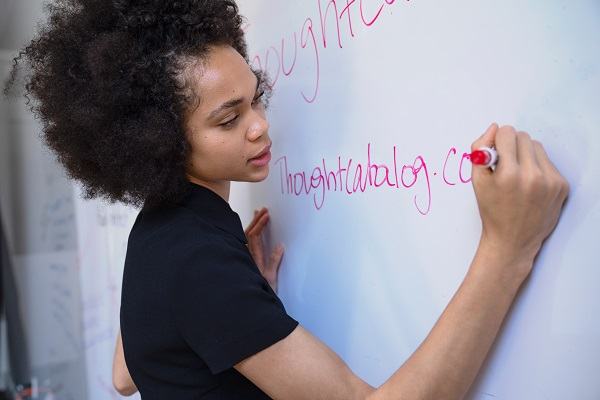Woman solving problems and writing on the whiteboard