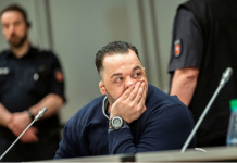 German nurse accused of killing a hundred patients apologizes to victims' relatives
