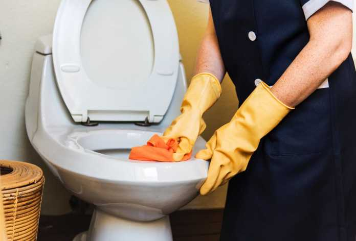 A person cleaning the toilet bowl.