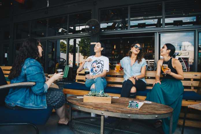 Four women sitting in a bench of a restaurant while laughing together.
