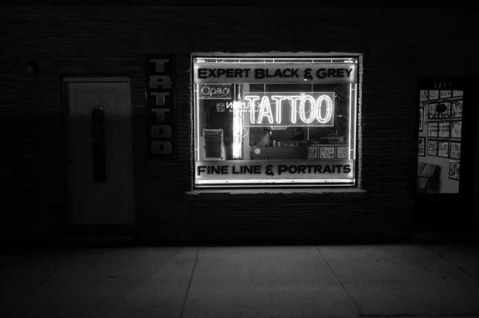 Grayscale photo of a tattoo shop signage.