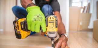 Handyman using Dewalt Cordless Impact Driver on brown board.