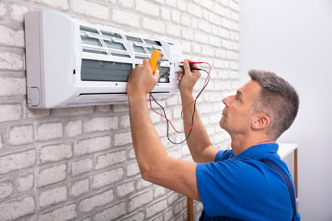 Male Electrician Checking Air Conditioner