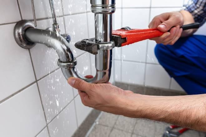 Male Plumber's Hand Repairing Sink Pipe Leakage