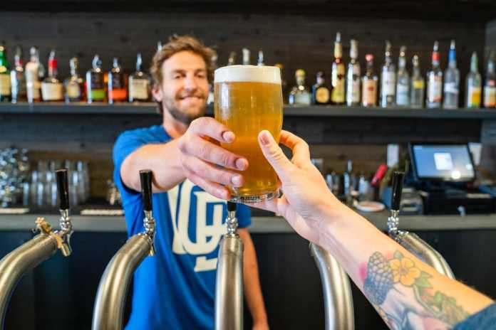 Man handing a glass of beer to someone.