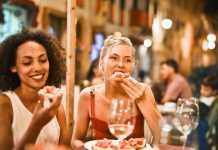 Two women eating pizza in an Italian restaurant.