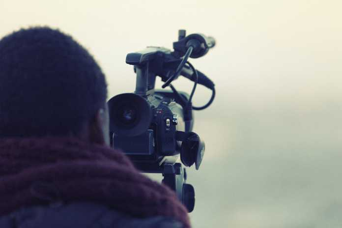 A videographer holding his camera while shooting