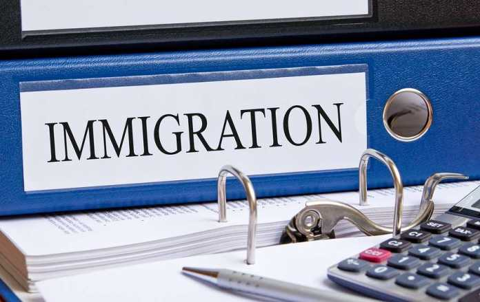 Blue binder with Immigration tag on desk in the office.