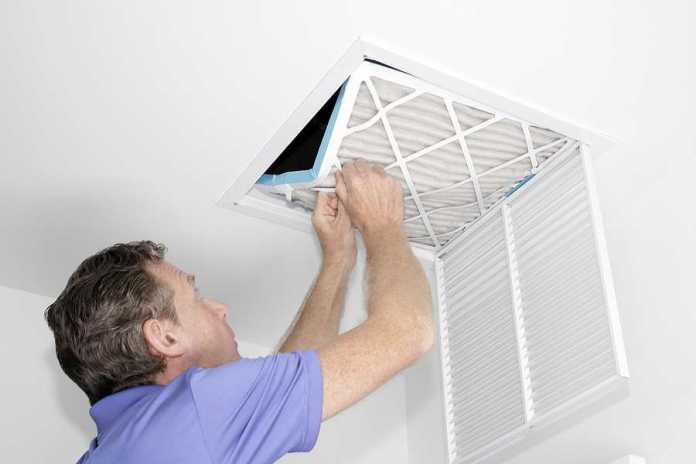 Man removing a dirty air filter in a house from a HVAC ceiling air vent.
