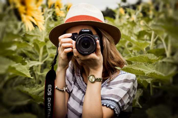 Woman holding a camera as she takes pictures.