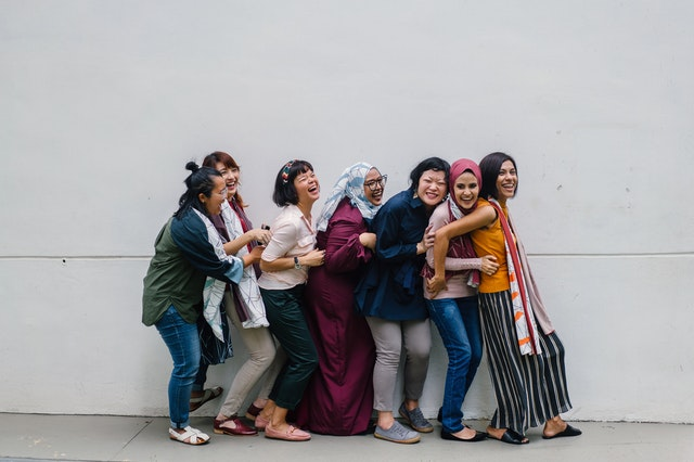 A group of women wearing basic wardrobe must haves standing in a line hugging and laughing.