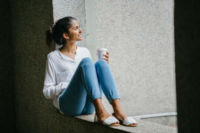 A woman sitting against a wall holding a coffee and looking away. She is wearing must have wardrobe basics a simple white shirt and jeans.