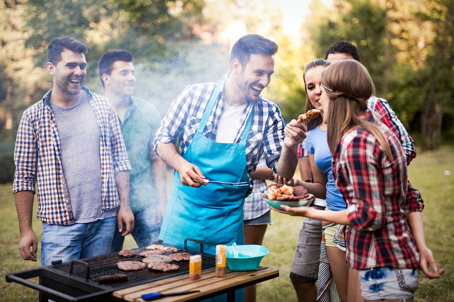 Friends having fun grilling meat enjoying bbq party