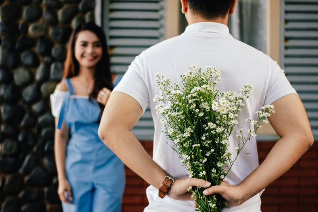 A man holding a bouquet of seasonal flowers bought online behind his back to hide them from his girlfriend.