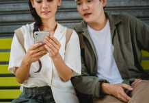 A woman holding a phone while a man looks and using in-app chat solutions.