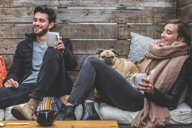 A man and a woman with cups of coffee getting cozy in their peaceful home with their dog.
